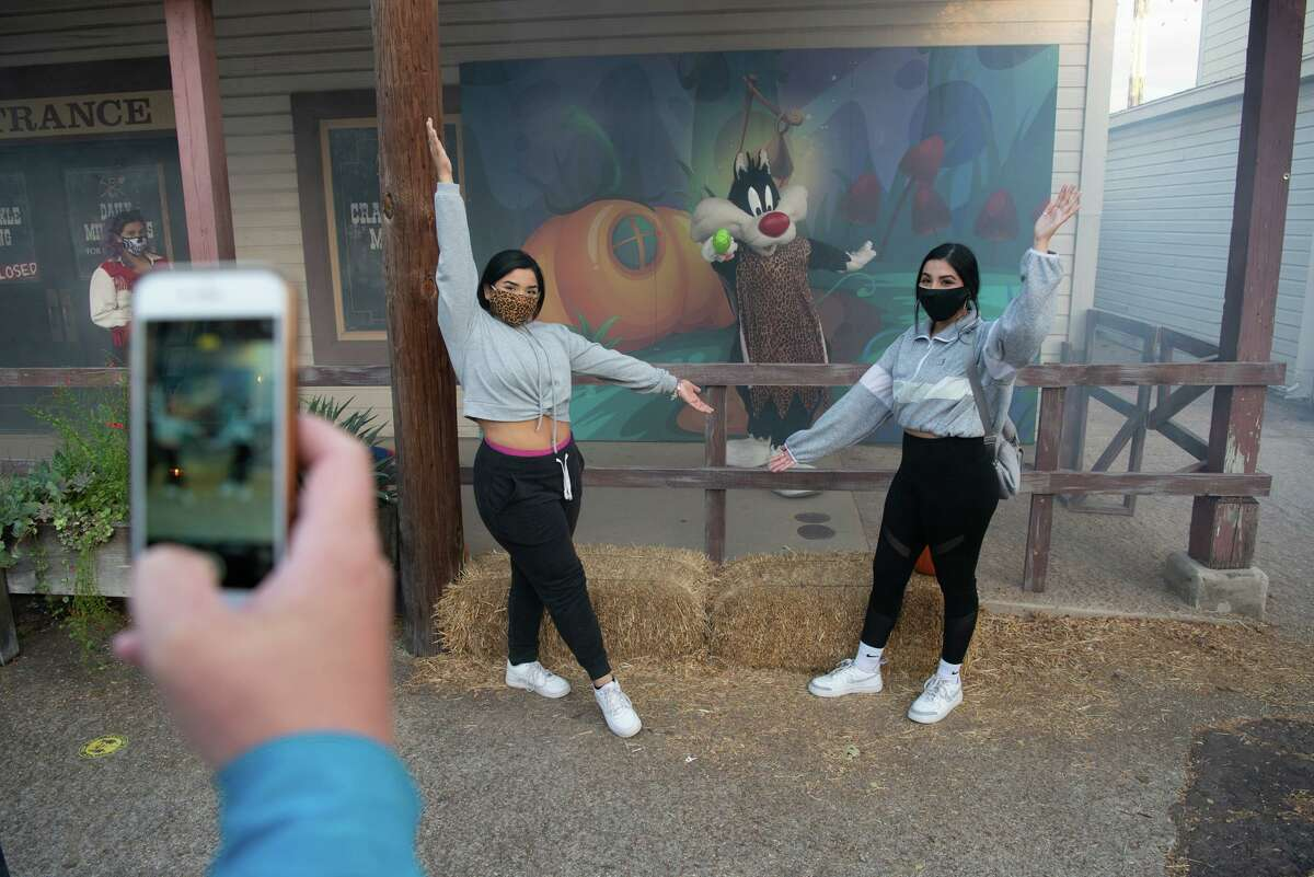 Iliana Guzman and Ashley Perez are socially distanced from Sylvester the Cat during Halloween activities at Six Flags Texas. The haunted houses have moved outdoors with social distancing and mask protocals in place.