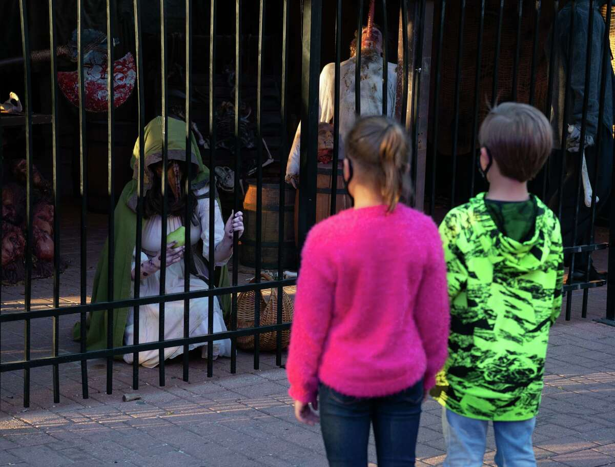Visitors look at the monsters during Halloween activities at Six Flags Texas. The haunted houses have moved outdoors with social distancing and mask protocals in place.