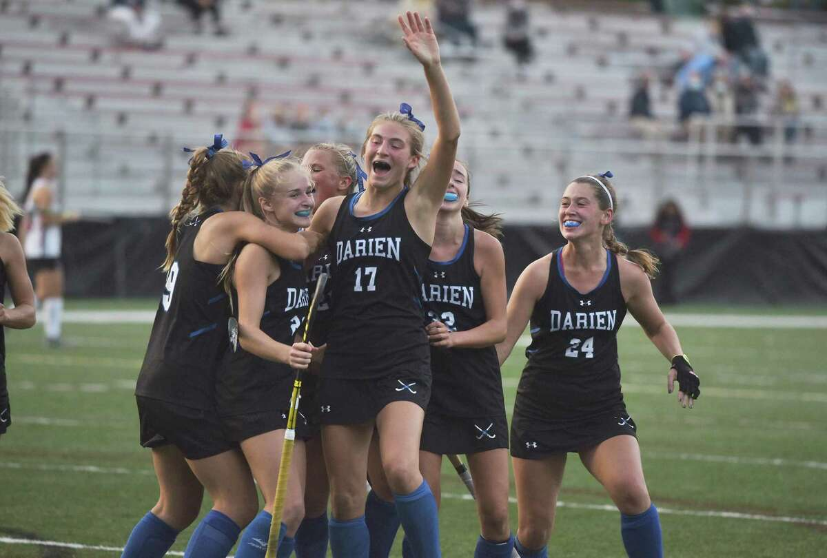 Darien field hockey players, including Blake Wilks (23), Morgan Massey (17), and Lindsey Olson (24), celebrate a third-period goal against New Canaan at Dunning Field on Monday.