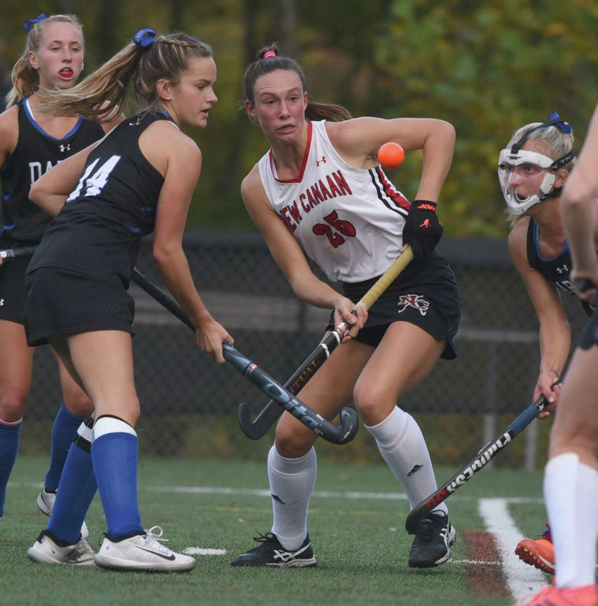 Darien's Emma Riley (14) and New Canaan's Polly Parsons (25) fight for the ball during a field hockey game at Dunning Field on Monday, Oct. 19, 2020.
