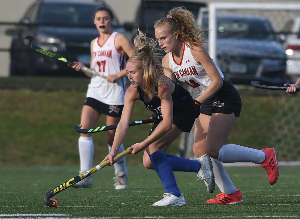 Darien's Blake Wilks controls the ball in front of New Canaan's Zoey Bennett during a field hockey game at Dunning Field on Monday.