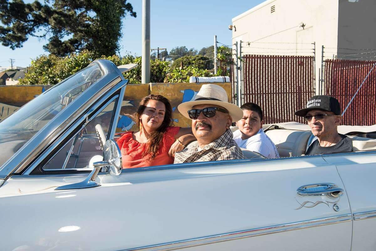 From left, Mariana, Roberto, Tito and Raul Hernandez drive through the San Francisco Lowrider Council's 6th annual Cold Frisco Nights in the Mission.