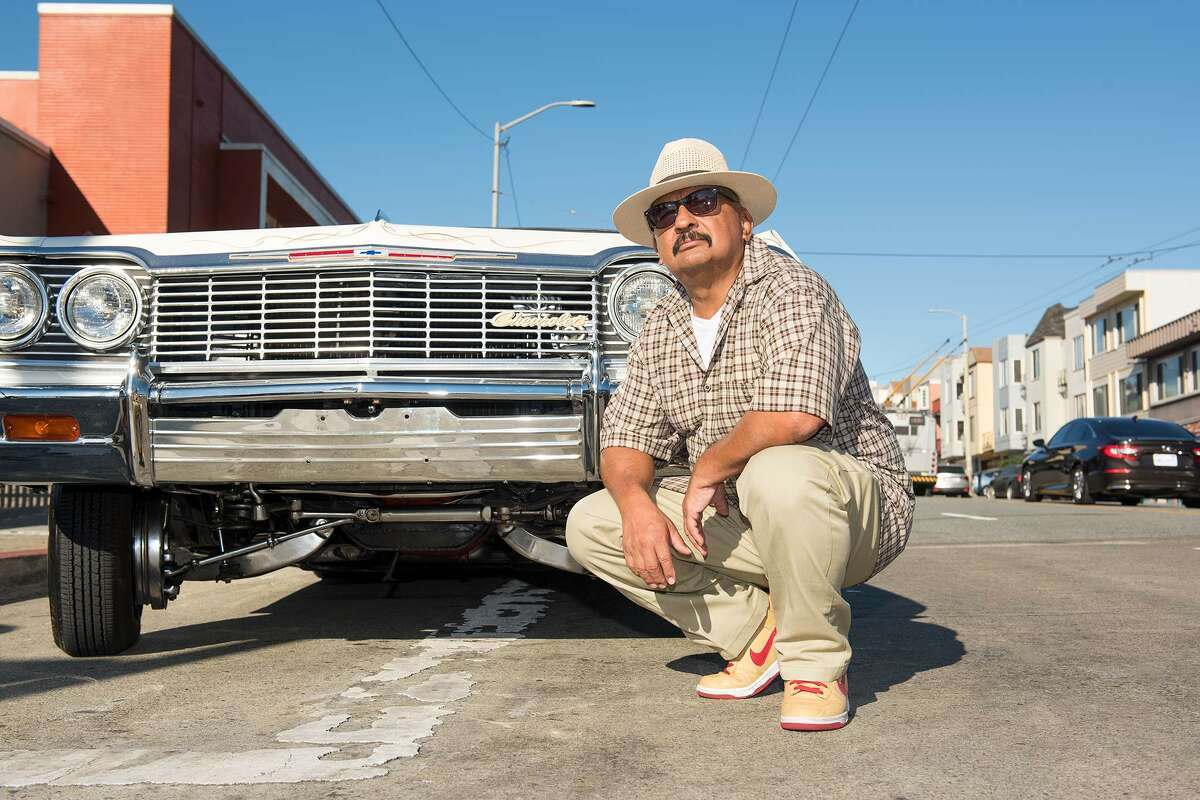 Roberto Hernandez, founder of the San Francisco Lowrider Council, poses in front of his Chevy Impala.