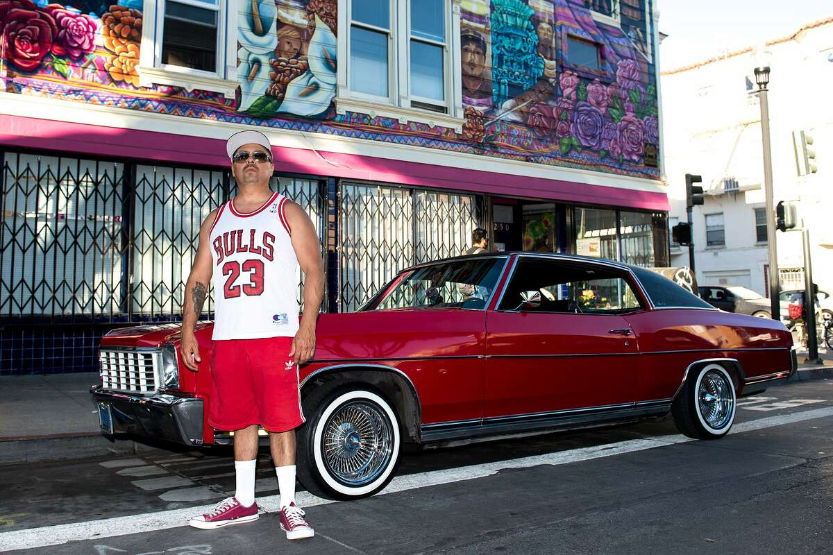 The San Francisco Lowrider Council gathered Saturday, Oct. 17, 2020, for their 6th annual Cold Frisco Nights in the Mission. Benjamin Bac Sierra stands by his 1972 Chevy Monte Carlo underneath a mural dedicated to people killed by the San Francisco Police Department.
