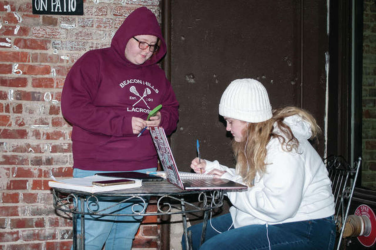 Emmy Treece (left) stands and listens to Morgan Pirkle as she works on her math homework in the cold Monday. Pirkle, a student at Illinois Wesleyan University in Bloomington, was tutoring Treece at The Soap Co. Coffee House in Jacksonville. Treece is a student at Franklin High School. According to AccuWeather, today's forecast is a high of 57 with a low of 46 and 60% chance of rain and a high of 62 on Wednesday. Thursday, however, it is expected to be a high of 80 and then dropping into to the 40s and 50s by the weekend.