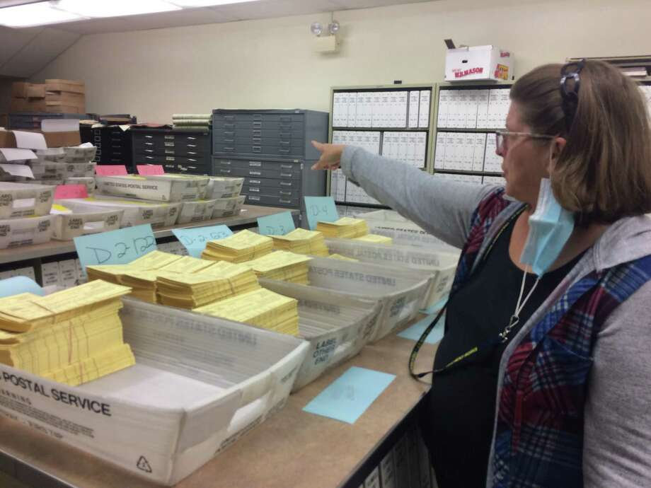 Assistant Town Clerk Susan Cole points to a stack of absentee ballots waiting to be mailed out on Monday. Photo: Donald Eng / Hearst Connecticut Media
