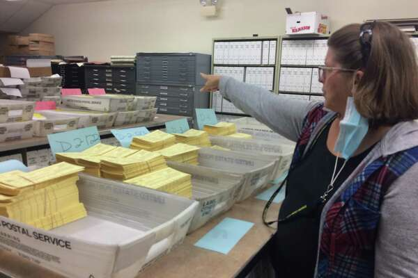 Assistant Town Clerk Susan Cole points to a stack of absentee ballots waiting to be mailed out on Monday.