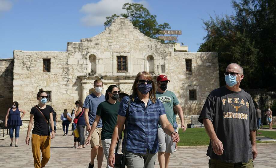Visitors wearing masks for protection from COVID-19 leave the recently reopened Alamo, Tuesday, Sept. 22, 2020, in San Antonio. The Texas Historical Commission is set to decide whether to allow the restoration and relocation of the Cenotaph, a 1930s-era stone monument to Texas revolutionaries killed in the Battle of the Alamo, as part of an effort to reclaim the historical footprint of the Alamo as part of a redevelopment plan. (AP Photo/Eric Gay) Photo: Eric Gay, Associated Press
