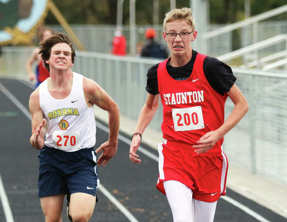 Staunton's Thomas Ogata (right) pushes to fend off a late surge from Roxana's Chris Holbrook in the final yards of the SCC Meet,s 5K cross country race Monday in Piasa. Ogata placed 17th, with Holbrook on his shoulder in 18th. Photo: Greg Shashack | The Telegraph