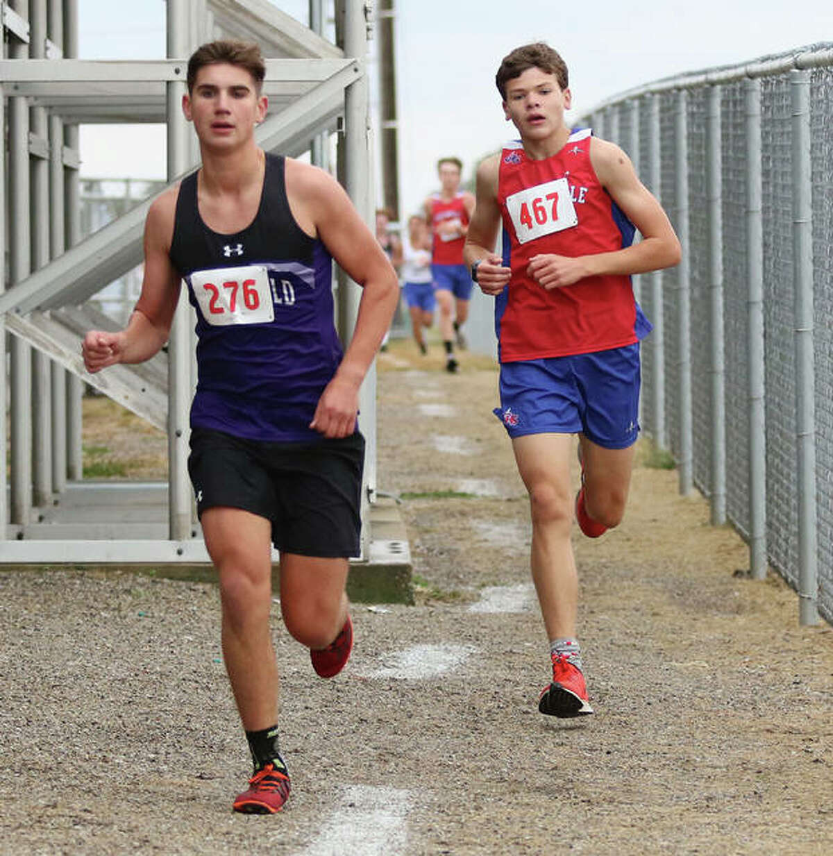 Litchfield's Camden Quarton (left) and Carlinville's Will Meyer run the narrow path behind the bleachers at Southwestern's football field Monday during the SCC Meet in Piasa. Quarton and Meyer held those positions in the final mile to finish second and third, respectively.