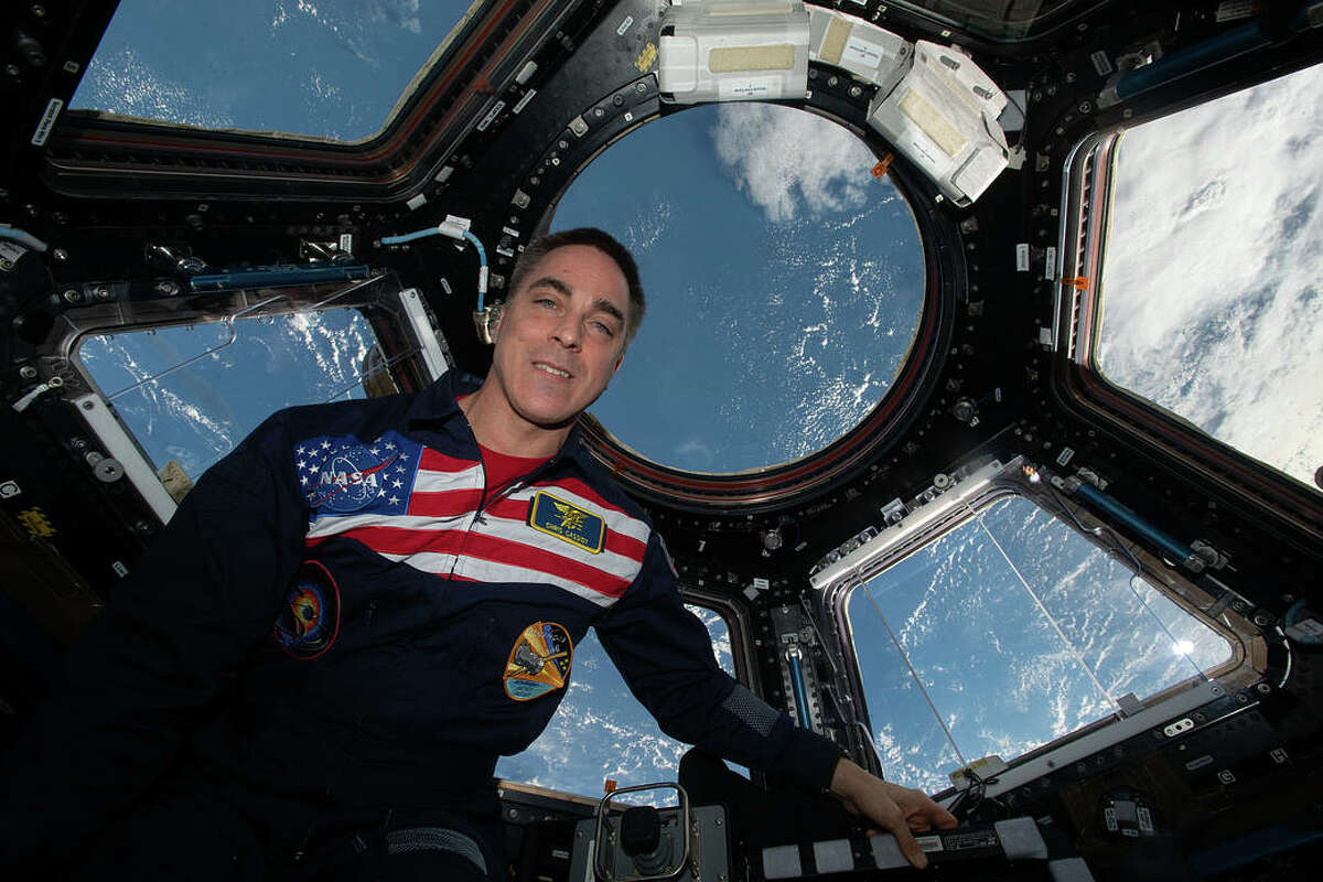 NASA astronaut and Expedition 63 Commander Chris Cassidy poses for a portrait wearing his flight suit inside the cupola, the International Space Station's window to the world. The orbiting lab was flying above the Pacific Ocean northeast of Papua New Guinea when this photograph was taken.