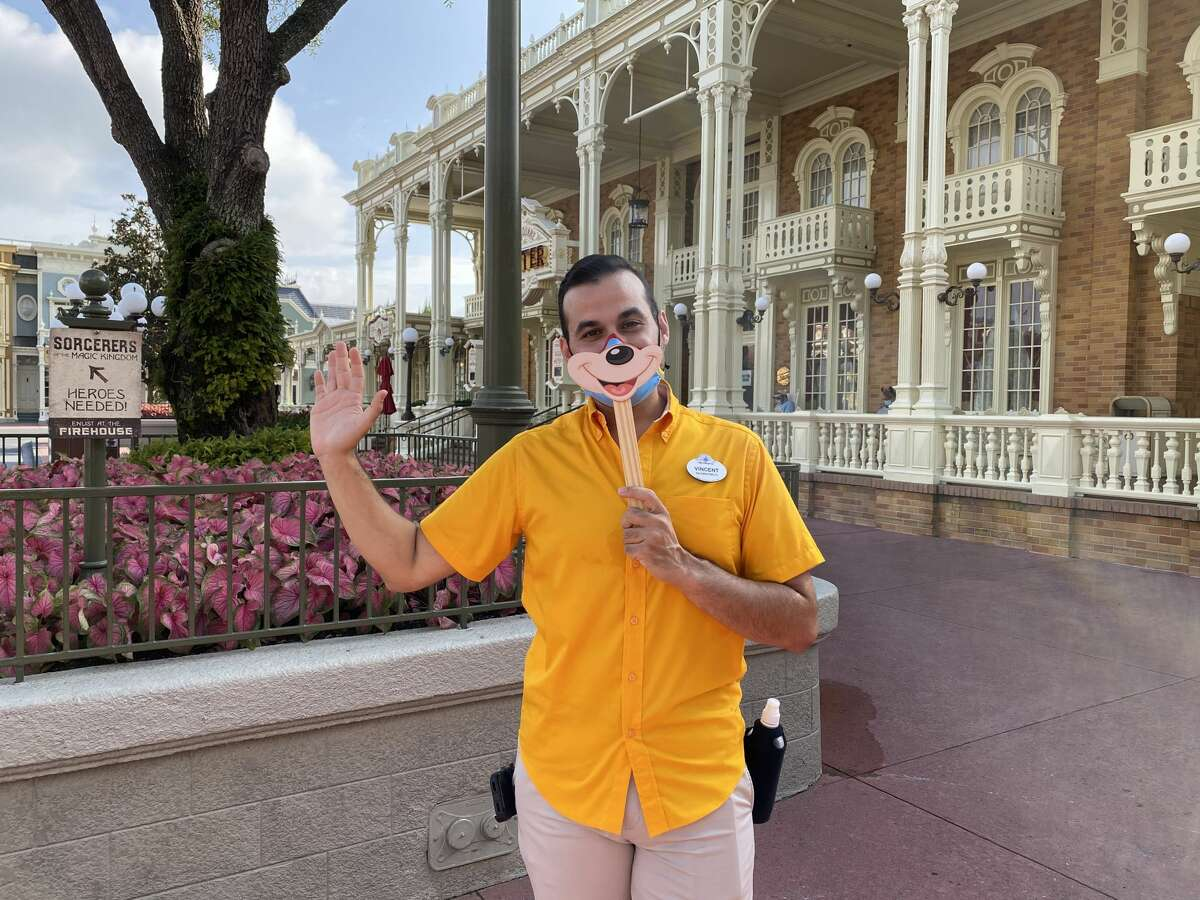A cast member holds a smiling sign over his mask on opening day of Magic Kingdom on July 11, 2020, at Walt Disney World in Orlando, Fla.
