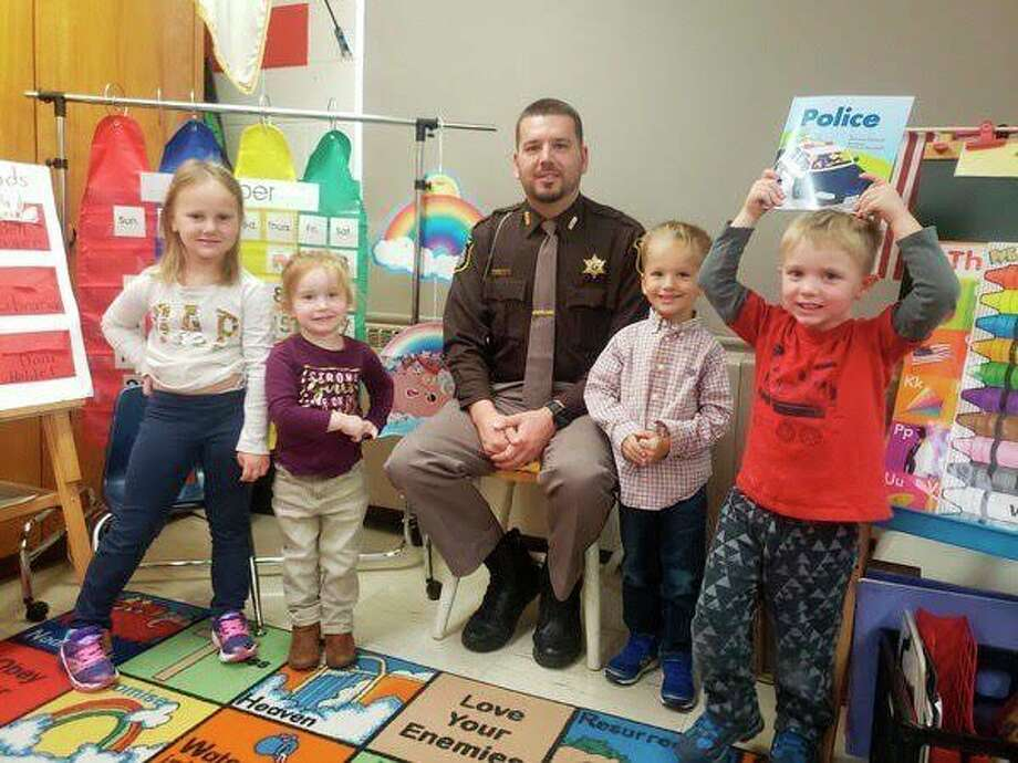 Manistee County Sheriff's Deputy Jason Traeger visited Trinity Lutheran School on Monday to meet with preschool students and read to them from a book about police officers. (Courtesy photo)