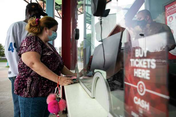 Moviegoers purchase tickets in August 2020 at an AMC Entertainment theater in Houston. On Oct. 20, 2020, AMC warned of the possibility of a bankruptcy by year end if it is unable to raise additional cash.