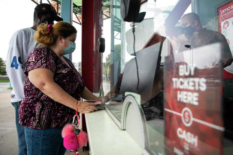 Moviegoers purchase tickets in August 2020 at an AMC Entertainment theater in Houston. On Oct. 20, 2020, AMC warned of the possibility of a bankruptcy by year end if it is unable to raise additional cash. Photo: Annie Mulligan / Contributor / © 2020 Annie Mulligan / Houston Chronicle