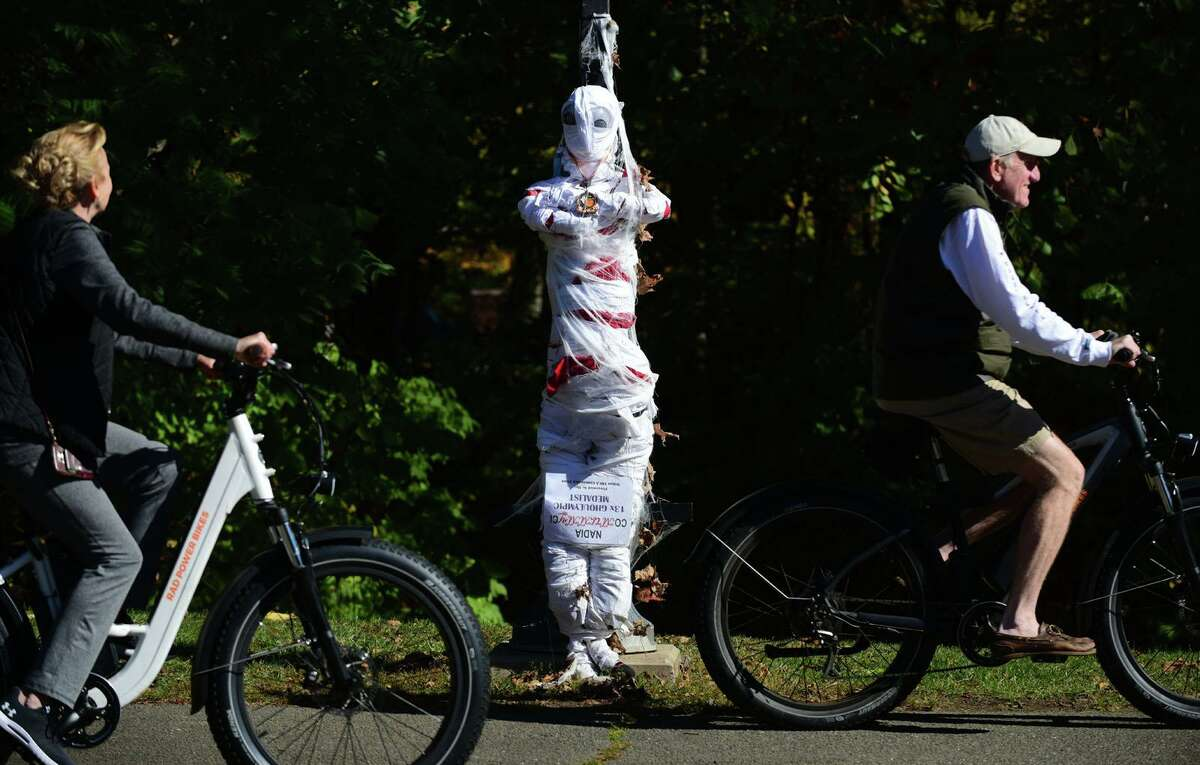 Cyclists ride by the entry from the Wilton YMCA Gymnastics team for the annual Scarecrow Fest on Saturday, Oct. 17, along River Road.