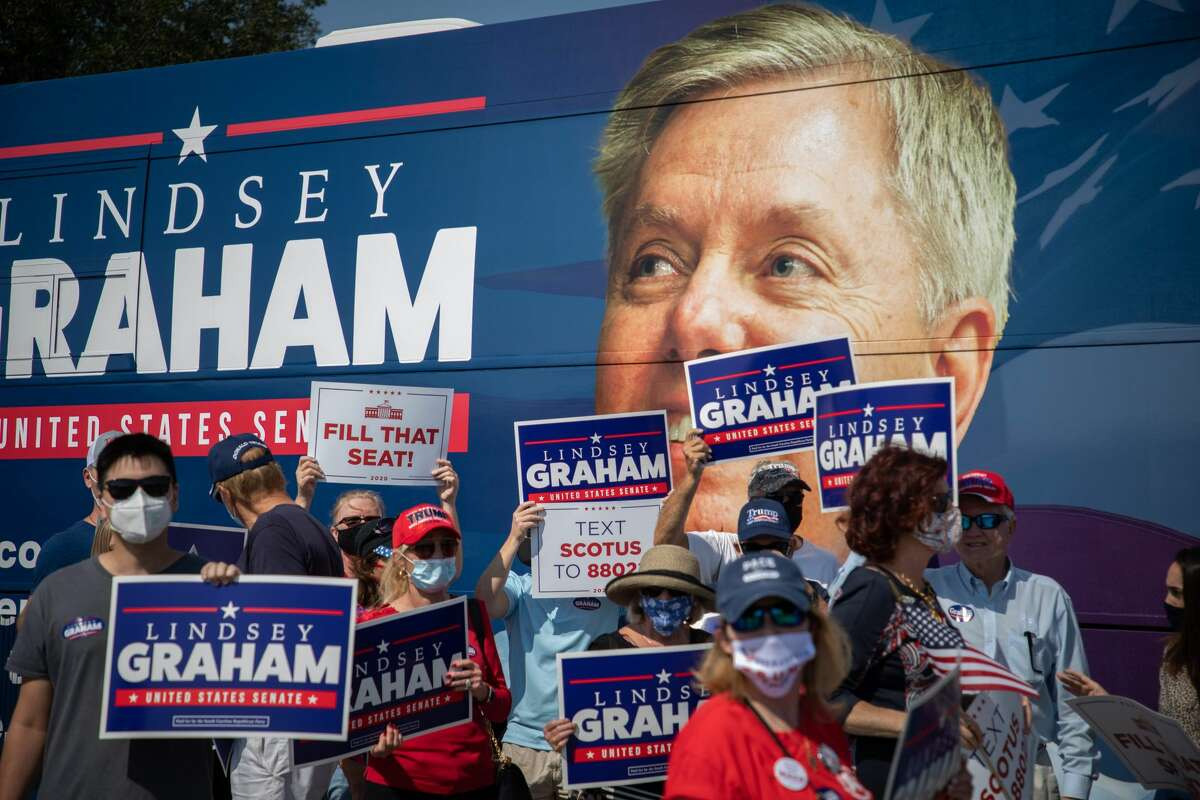 Supporters of US Senator Lindsey Graham hold up signs as he arrives to address supporters during a get out the vote rally at the Charleston Coliseum and Convention Center in North Charleston, South Carolina on October 16, 2020. - An epic political battle is climaxing in South Carolina, where presidential ally Senator Lindsey Graham is neck-and-neck with an African-American challenger two decades his junior, raising Democratic hopes that they can snatch a Senate seat in Trump country. Out-fundraised by Democrat Jaime Harrison, and glued to President Donald Trump's hip on issues like immigration and Supreme Court nominations, Graham is under threat like never before in a state where his Republican Party has controlled the local legislature, governor's mansion and both US Senate seats for the past 15 years. (Photo by Logan Cyrus / AFP) (Photo by LOGAN CYRUS/AFP via Getty Images)