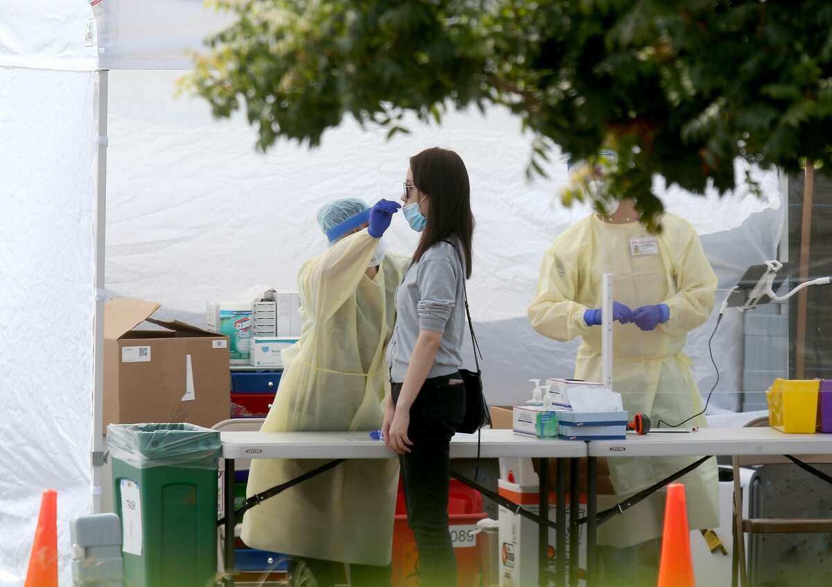 A woman gets tested at a COVID-19 test site at Madison Park in downtown Oakland, Calif., on Tuesday, Sept. 15, 2020. Asian Health Services has partnered with Alameda County to manage the site, which offers services in 12 languages.