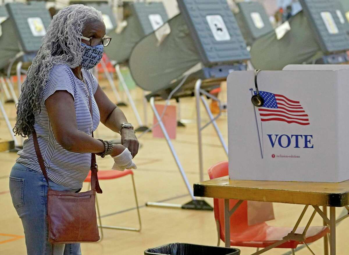A voter takes off gloves after voting at the Metropolitan Multi-Services Center, 1475 W. Gray St., during the first day of early voting Tuesday, Oct. 13, 2020 in Houston.