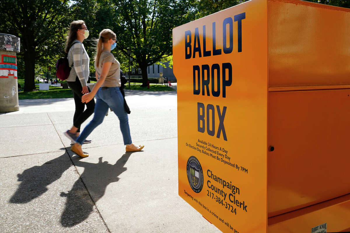 University of Illinois students walk past a mail-in ballot drop box that sits on the northwest corner of the university in Urbana. The new drop box option was authorized as part of a new state law signed by Gov. J.B. Pritzker in June to expand early voting options and help reduce the number of people who would otherwise vote in person in the midst of the COVID-19 pandemic.