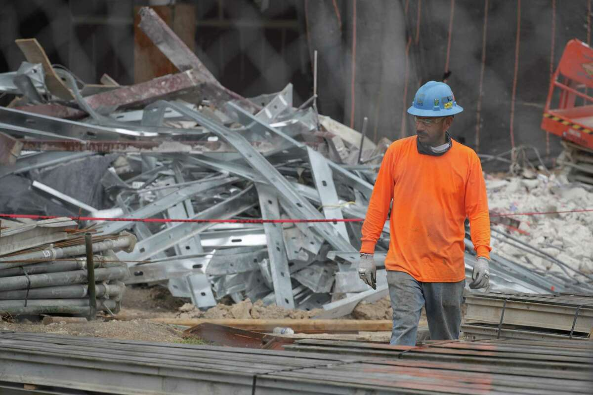 A worker walks past debris from the deadly construction collapse inside the future headquarters of Marathon Oil Corporation Thursday, Oct. 8, 2020, in Houston.