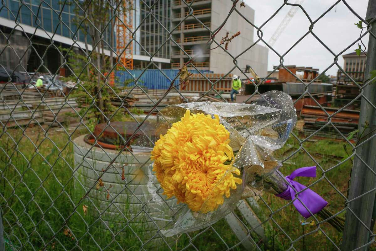 A small bouquet of flowers in the fence at the sight of a deadly construction collapse inside the future headquarters of Marathon Oil Corporation Thursday, Oct. 8, 2020, in Houston.