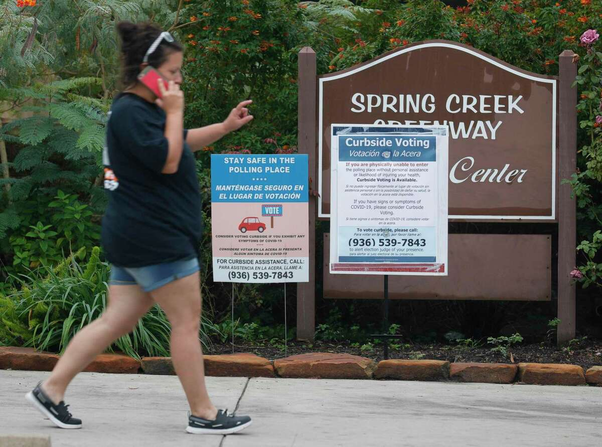 A woman walks past a curbside voting sign at the Spring Creek Greenway Nature Center, Tuesday, Oct 20, 2020 in Spring. Montgomery County commissioners unanimously approved opening early voting centers at the nature center and East Montgomery County Court Annex during a special meeting Monday, Oct. 19, as voter turnout continues to sore surpassing 2016 totals by just over 4,100 in the first five days of early voting.