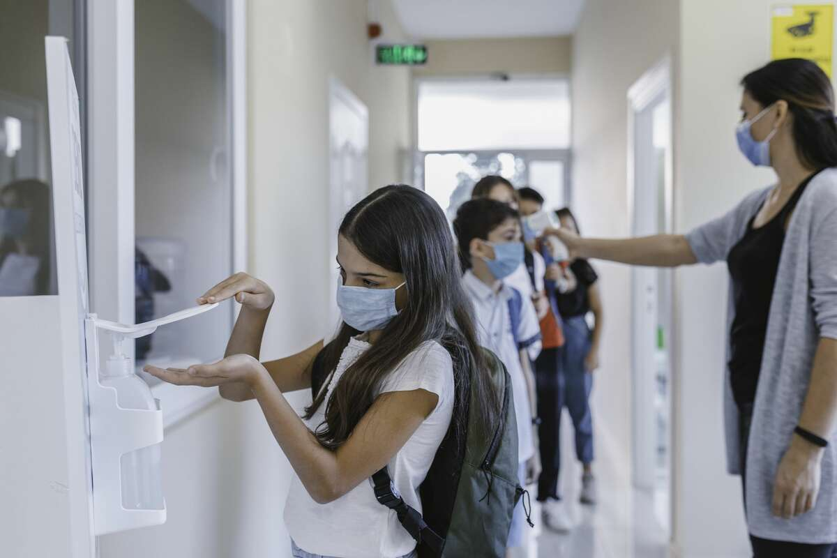 Little girl student wearing a surgical face mask pumping hand sanitizer into her hands for taking care of hand hygiene after checking temperature line up and entering into classroom in COVID-19 outbreak at reopen elementary school entrance after coronavirus quarantine and lockdown