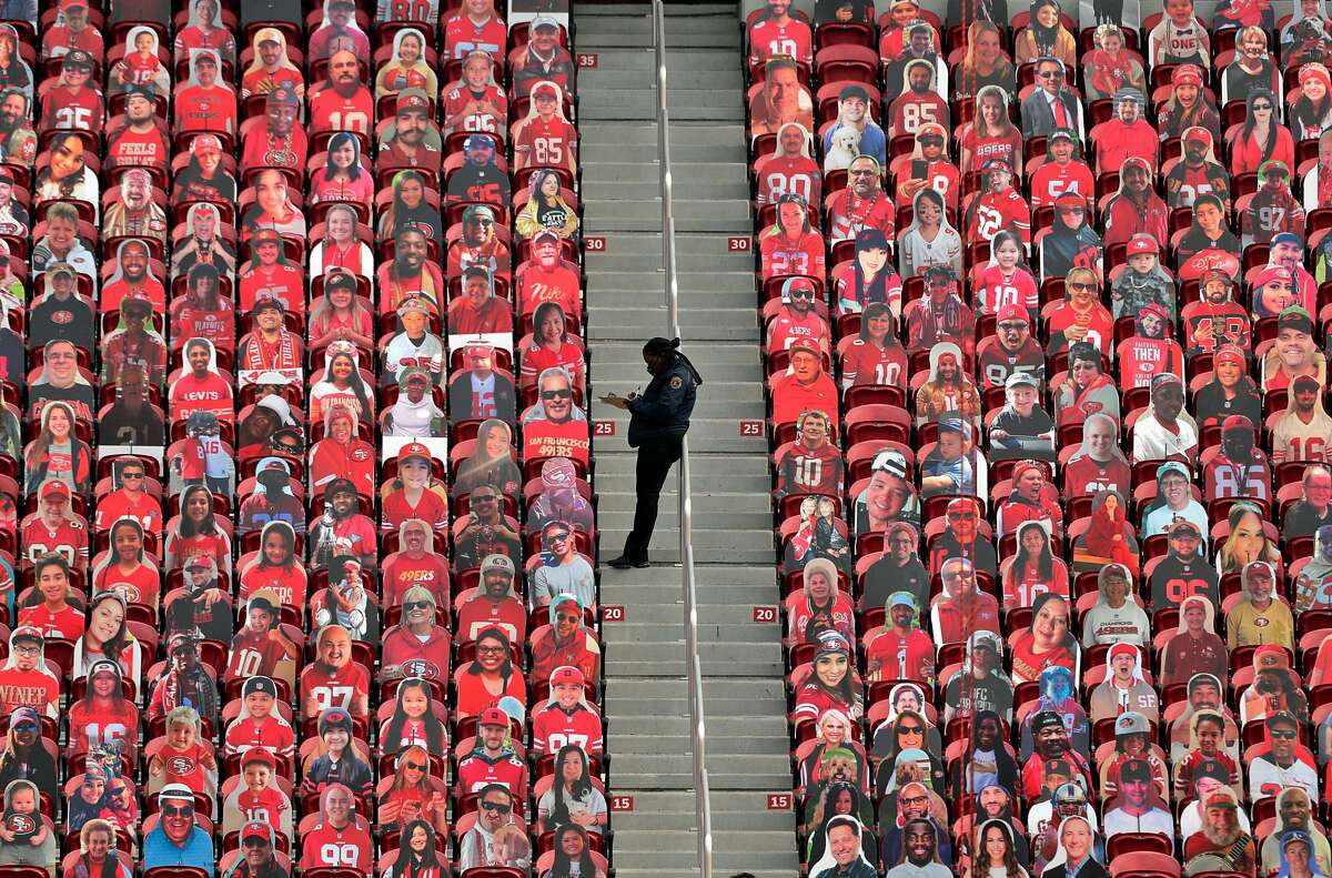 A security guard fills out paperwork amid fan cutouts behind the end zone in the second half as the San Francisco 49ers played the Arizona Cardinals at Levi's Stadium in Santa Clara, Calif., on Sunday, September 13, 2020.