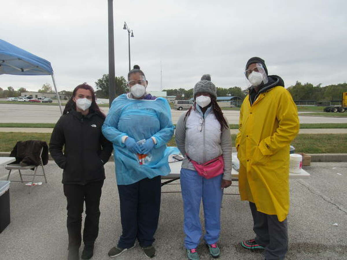 From left, Kaylee Camillo, Amica McIntee, Kindness Singano and Jermone Jones await participants at coronavirus testing Tuesday at Lewis and Clark Community College in Godfrey.