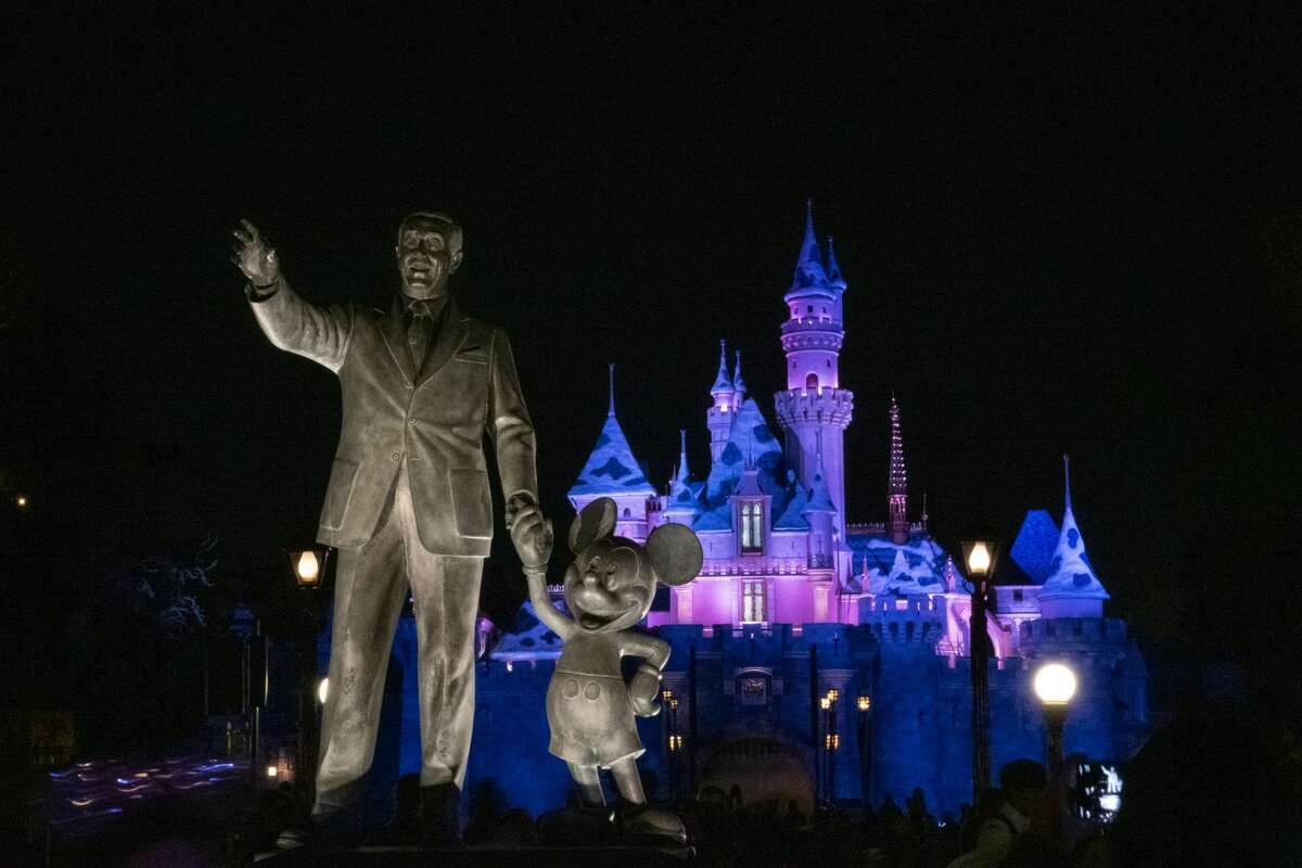 ANAHEIM, CA - JANUARY 13: A general view of the Walt Disney and Mickey Mouse statue in front of the Sleeping Beauty Castle lit up at night at Disneyland Park on January 13, 2020, in Anaheim, California.