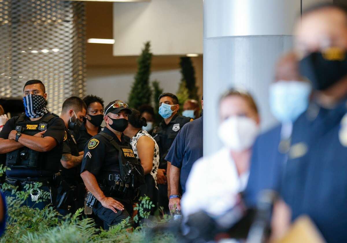 Houston Police officers watch as chief Art Acevedo talks to reporters about the death of Sgt. Harold Preston, at Memorial Hermann Hospital on Tuesday, Oct. 20, 2020, in Houston. Two officers were shot by a suspect during a domestic violence call at an apartment complex near El Rio and Holly Hall streets.