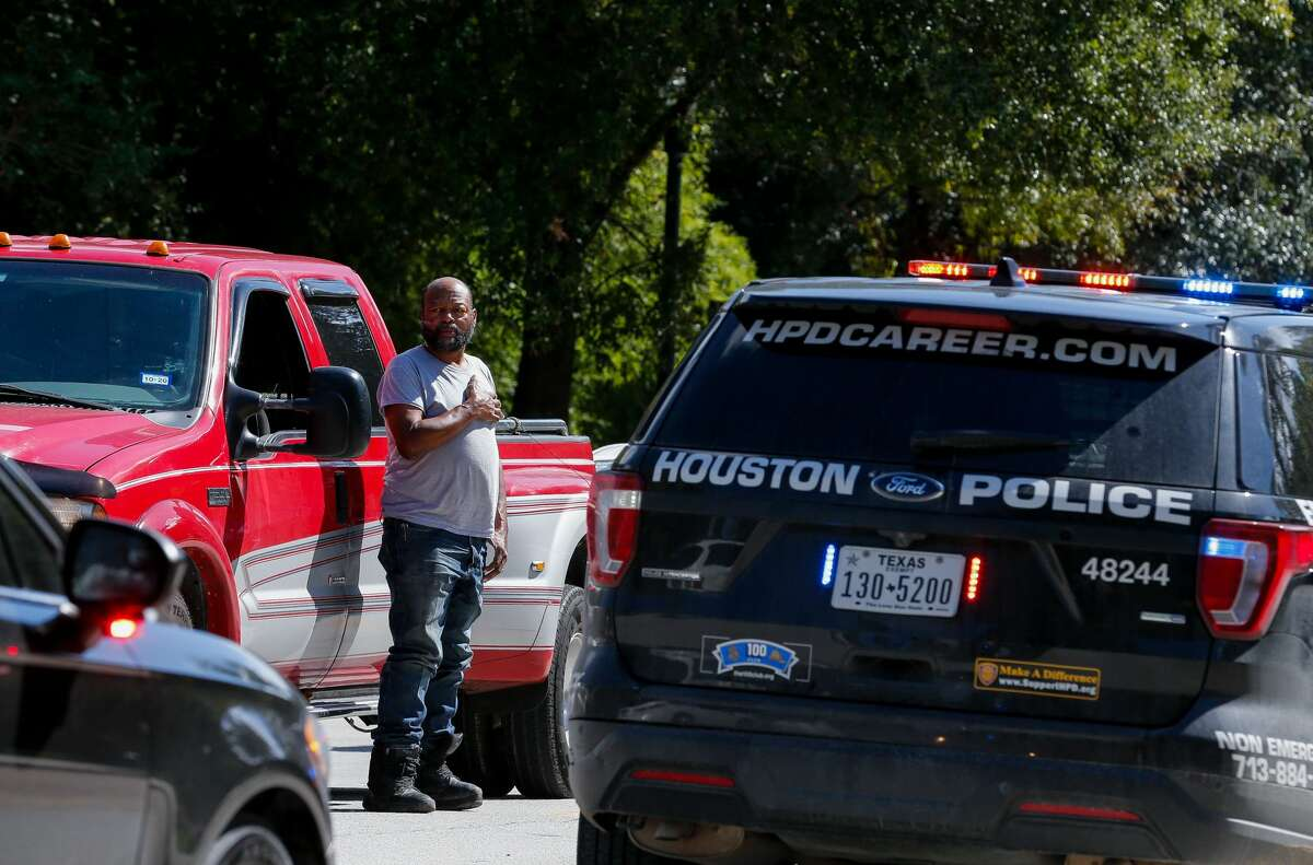 Dwight Randall stands outside his vehicle to watch the motorcade escorting the body of Houston Police Sgt. Harold Preston from Memorial Hermann Hospital to the medical examiner's office on Tuesday, Oct. 20, 2020, in Houston. Two officers were shot by a suspect during a domestic violence call at an apartment complex near El Rio and Holly Hall streets.