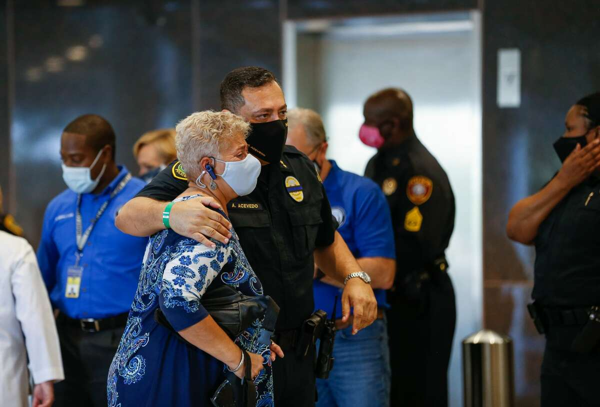 Houston Police chief Art Acevedo comforts Council Member Carolyn Evan Shabazz outside Memorial Hermann Hospital after the death of Sgt. Harold Preston on Tuesday, Oct. 20, 2020, in Houston. Two officers were shot by a suspect during a domestic violence call at an apartment complex near El Rio and Holly Hall streets.