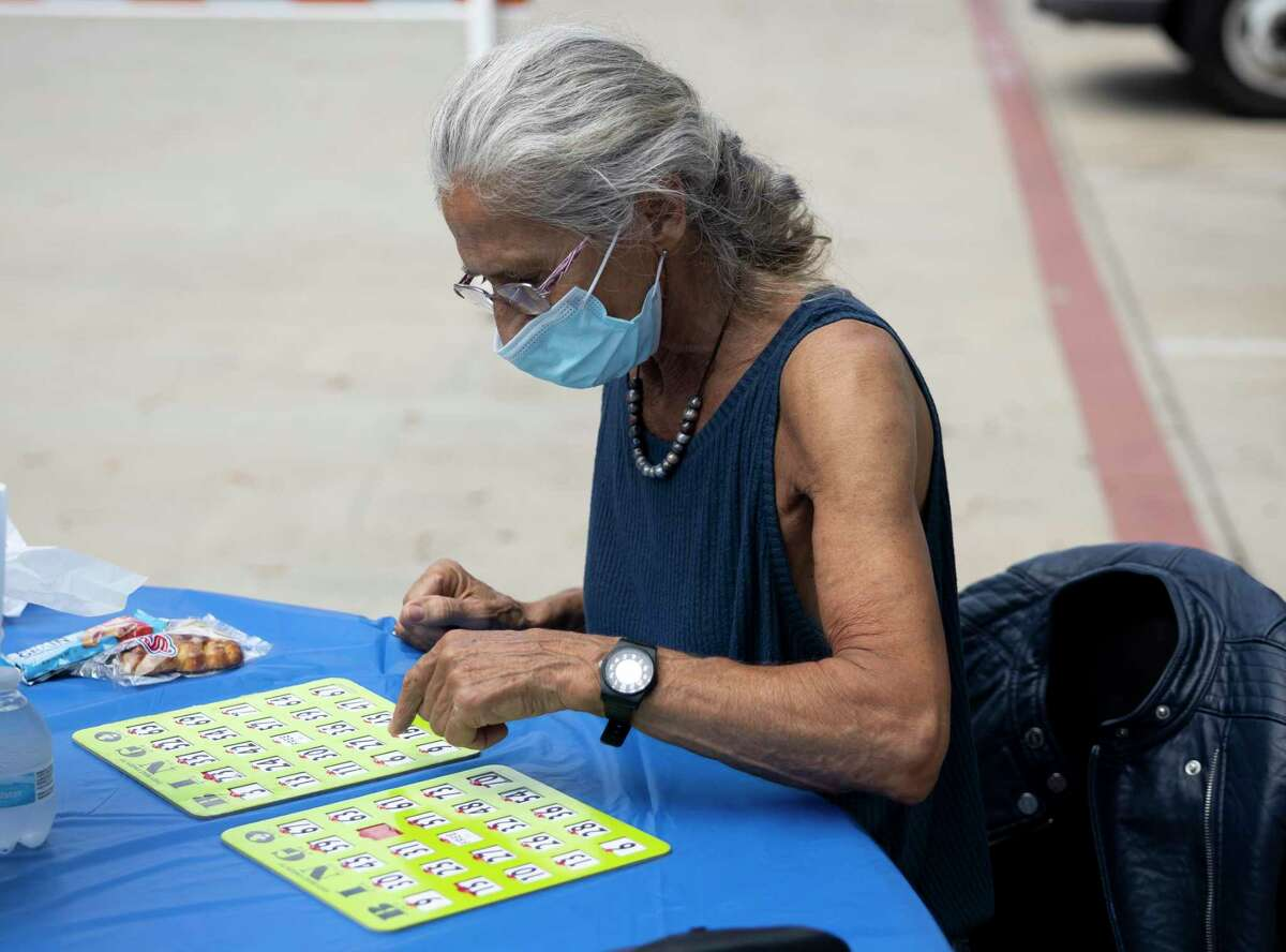 Patricia Plasse-Fauque plays a round of bingo during an event hosted by the Conroe Senior Center called the Parking Lot Party at Candy Cane Park, Tuesday, Oct. 20, 2020, in Conroe. Participants were able to play bingo, receive prizes and enjoy a complimentary lunch from Red Brick Tavern.