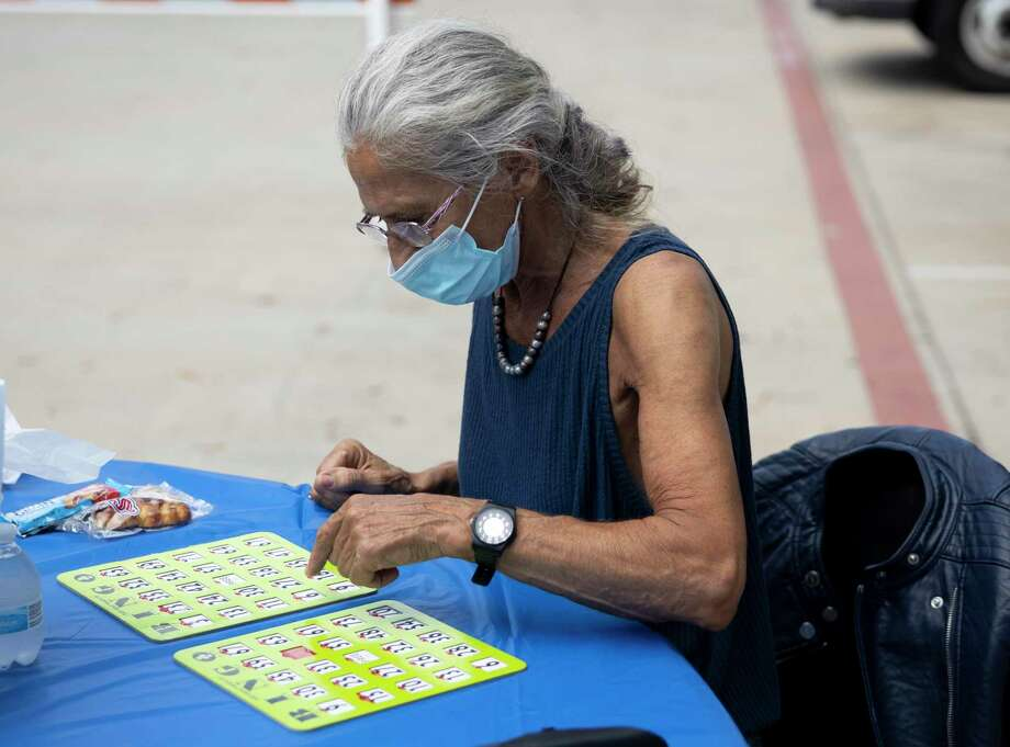 Patricia Plasse-Fauque plays a round of bingo during an event hosted by the Conroe Senior Center called the Parking Lot Party at Candy Cane Park, Tuesday, Oct. 20, 2020, in Conroe. Participants were able to play bingo, receive prizes and enjoy a complimentary lunch from Red Brick Tavern. Photo: Gustavo Huerta, Houston Chronicle / Staff Photographer / 2020 © Houston Chronicle