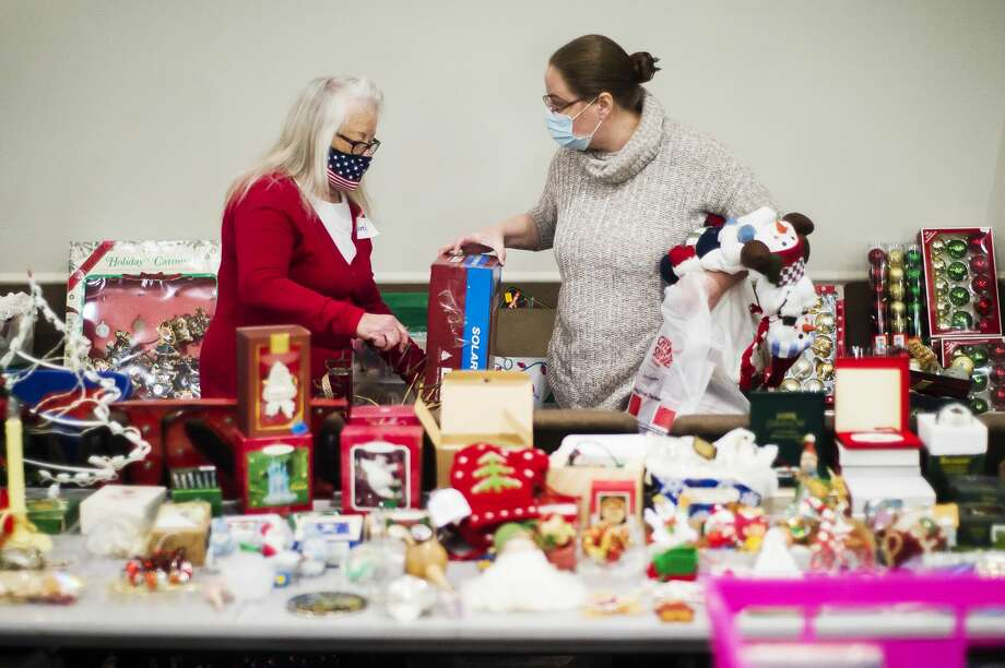 Volunteer Carol Artcliff, left, assists Cassandra Robnett, right, as Robnett peruses new and gently used holiday decorations during a donation drive for flood victims Monday, Oct. 19, 2020 at Abundant Life Apostolic Church of Sanford. (Katy Kildee/kkildee@mdn.net) Photo: (Katy Kildee/kkildee@mdn.net)
