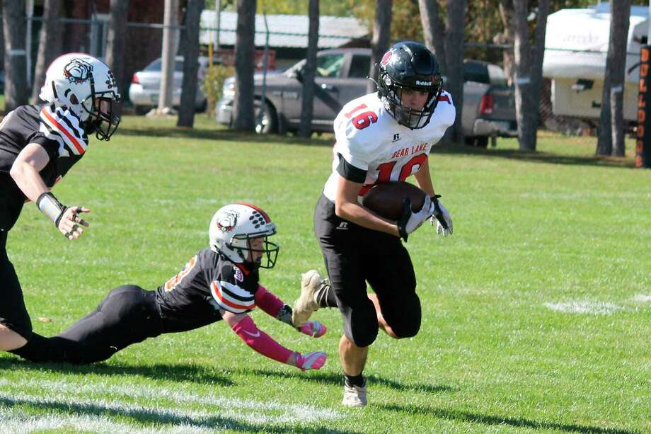 Bryce Harless breaks a tackle while running the ball against Mesick on Oct. 10. (File photo)