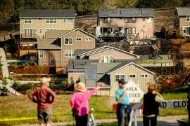 Following the Glass Fire, Skyhawk neighborhood residents stop to examine burned homes on Tuesday, Oct. 6, 2020, in Santa Rosa, Calif.