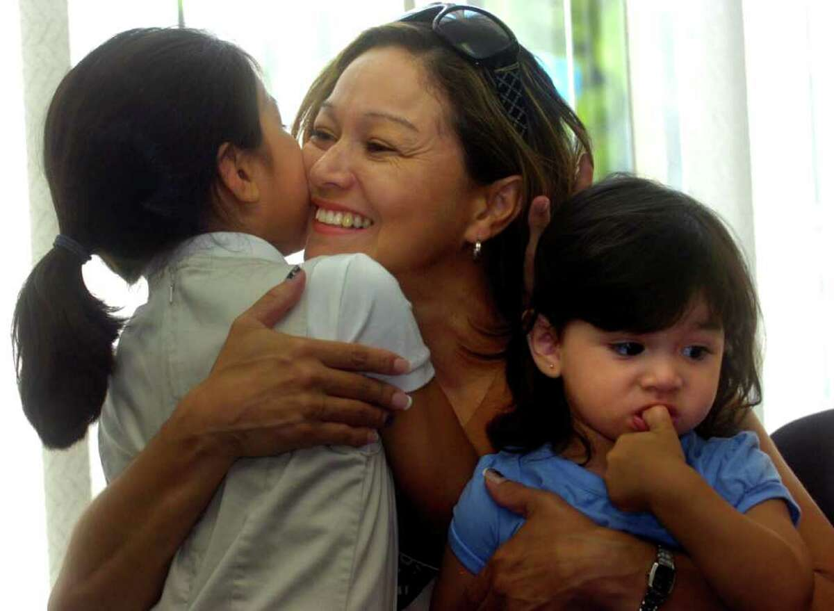 Cynthia Trejo, center, reacts to winning the lottery for a home she bid on as she hugs her daughters Danniela, 7, left, and Maureen, 2, right, at the Housing Development Fund office in Bridgeport on Tuesday, August 31, 2010.