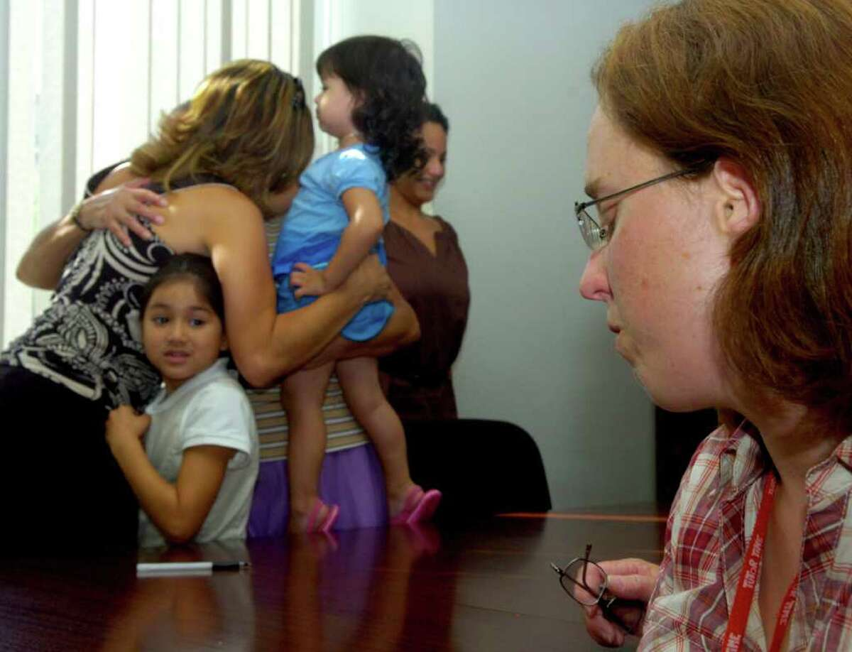 The Trejo family, left, celebrates winning the Housing Development Fund lottery for the house they bid on as Sara McGarry, front, shows her disappointment at losing the house on Tuesday, August 31, 2010.