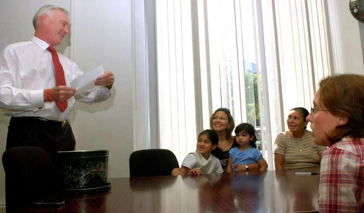 Bridgeport Mayor Bill Finch draws a name out of a hat to determine who will win a home claimed by equal bids by the Trejo family, back, and Sara McGarry, front, at the Housing Development Fund office in Bridgeport on Tuesday, August 31, 2010.