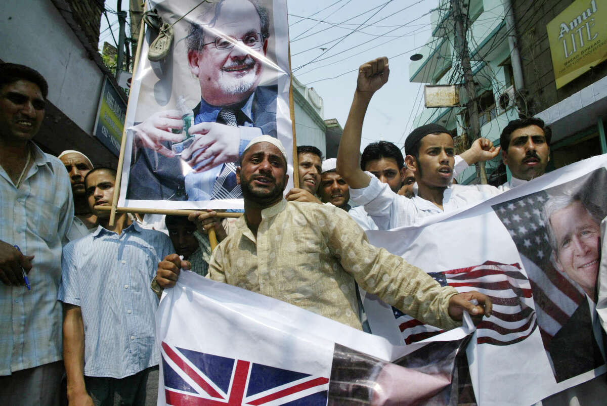 Muslim protestors hold posters of British Prime Minister Tony Blair, half seen left bottom, and U.S. President George W. Bush, right, before burning them, as they shout slogans against author Salman Rushdie, seen in poster in background, during a protest in Jammu, India, Friday, June 22, 2007. Most shops, offices and schools were closed Friday in India's Muslim-majority Kashmir region to protest Britain awarding a knighthood to Rushdie, who has been accused of insulting Islam. (AP Photo/Channi Anand)
