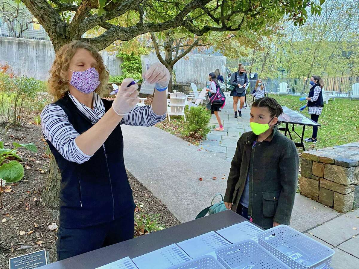 Michelle Summers, Greenwich Academy's director of finance and operations - and COVID coordinator - collects saliva samples for testing at the private school in Greenwich.