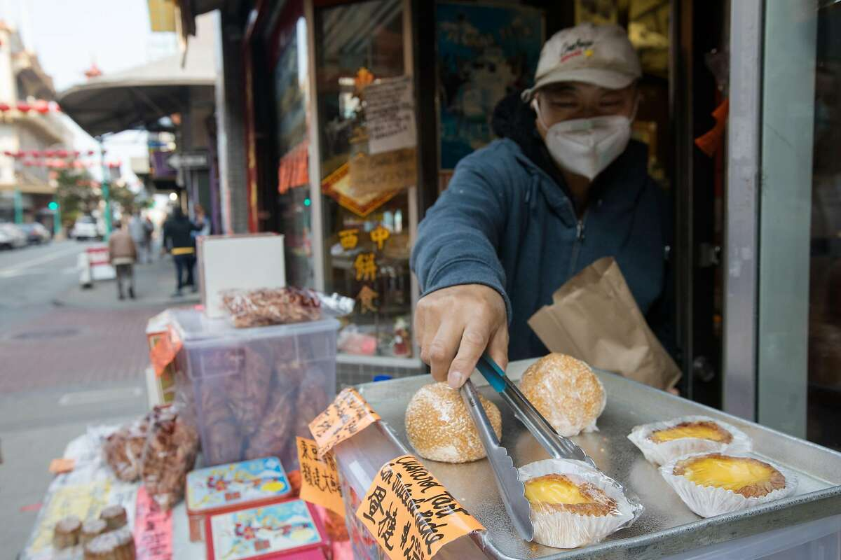 Eastern Bakery owner Orlando Kuan bags some custard tarts bought by a customer in front of his store on Grant Avenue in Chinatown in San Francisco on Oct. 7, 2020.