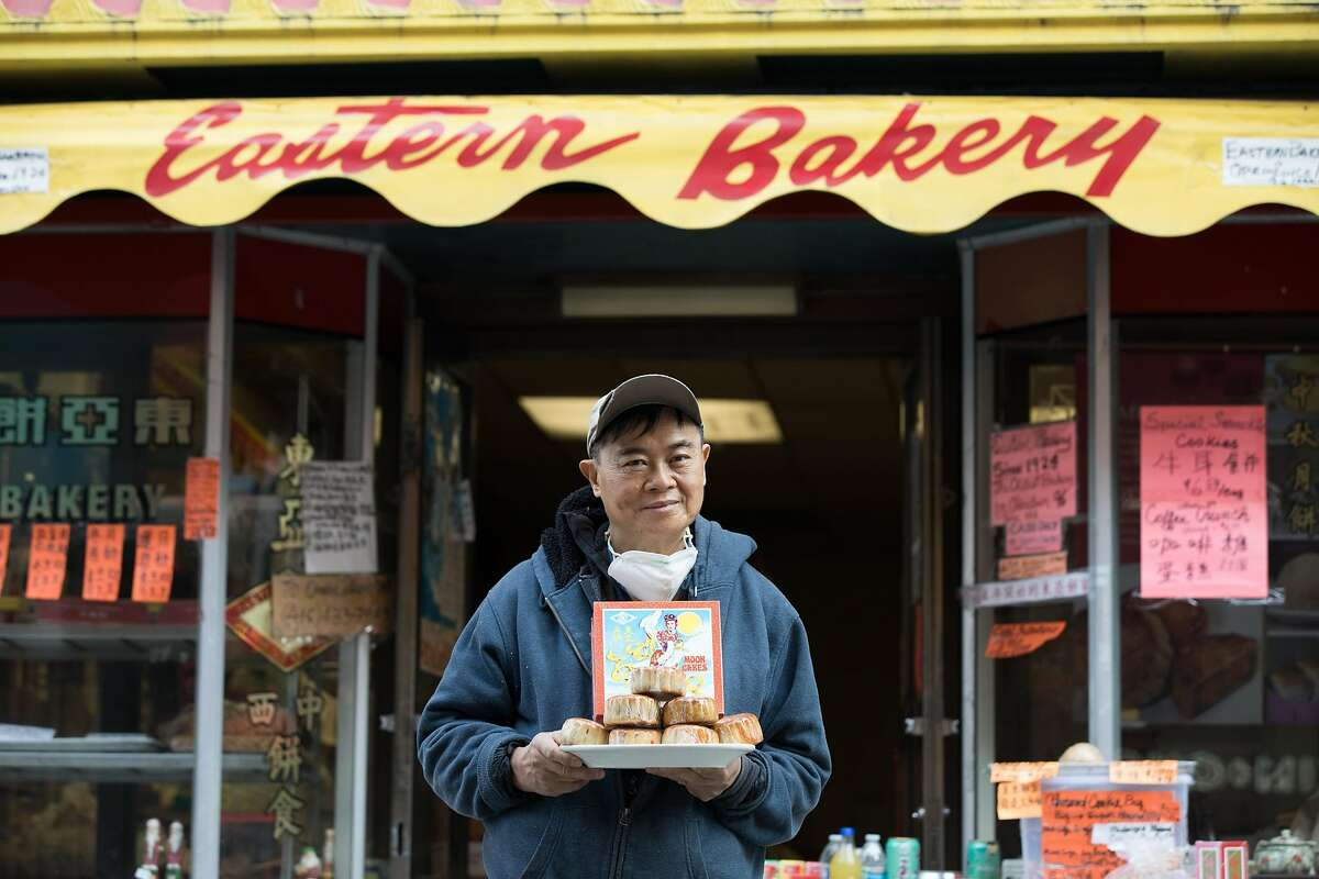 Eastern Bakery owner Orlando Kuan holds some of his bakery's freshly made lotus mooncakes in front of his store on Grant Avenue in Chinatown in San Francisco on Oct. 7, 2020.