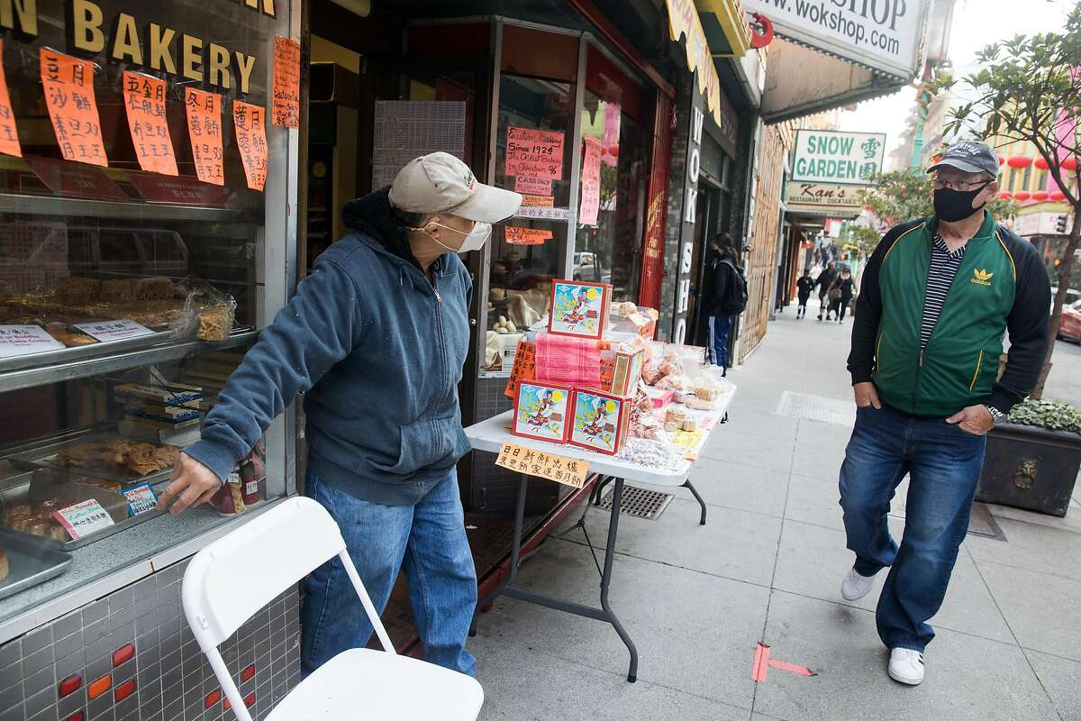 Owner Orlando Kuan points out some pastries in the window to a pedestrian walking by Eastern Bakery in Chinatown in San Francisco on Oct. 7, 2020.
