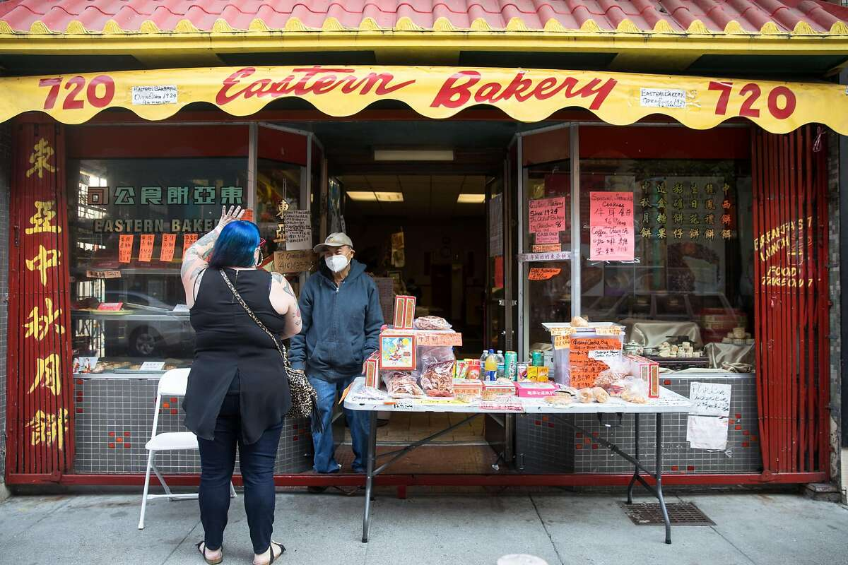 Customer Megan McGwire, left, waves goodbye to Eastern Bakery owner Orland Kuan after buying pastries at the Chinatown bakery in San Francisco on Oct. 7, 2020.