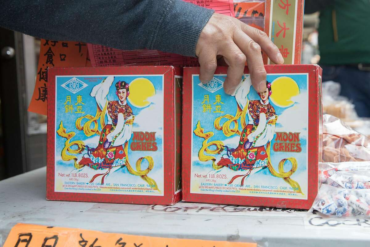 Owner Orlando Kuan sets up a display of Eastern Bakery's mooncakes outside his store in Chinatown in San Francisco on Oct. 7, 2020.