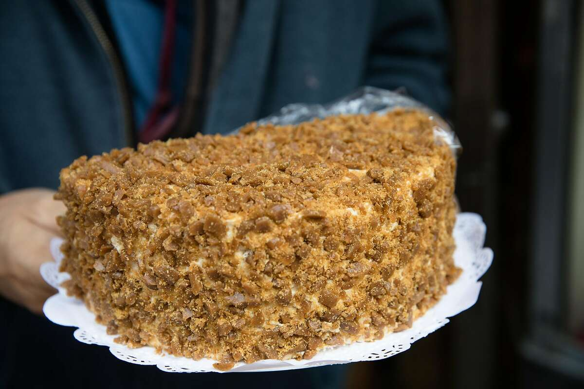Owner Orlando Kuan displays the Eastern Bakery's coffee crunch cake outside his store in Chinatown in San Francisco on Oct. 7, 2020.